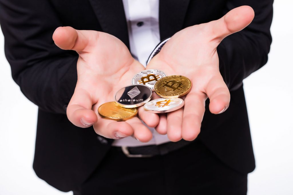 A suited man displaying different types of crypto coins in his hands