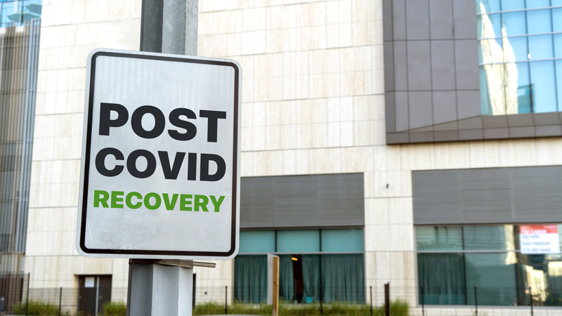 Signboard outside office building reads 'POST COVID RECOVERY'